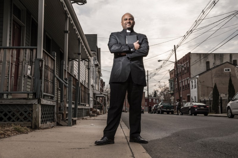 Armstrong stands on a street curb, dressed in all-black reverend attire. Surrounding him are run-down buildings. The sky is dark gray and power lines run overhead.
