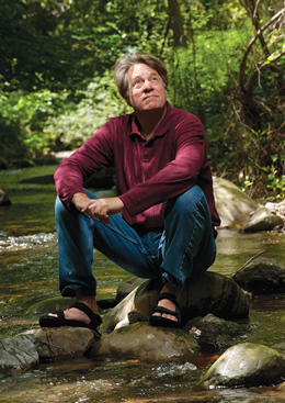 Dave Eshelman. He is sitting on a rock outcropping in the middle of a stream.