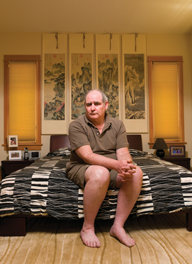 John Mark, sitting on his bed in a well-designed, artful home.