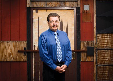 Richard Yacco stands in front of an old, barred door wearing standard work attire.