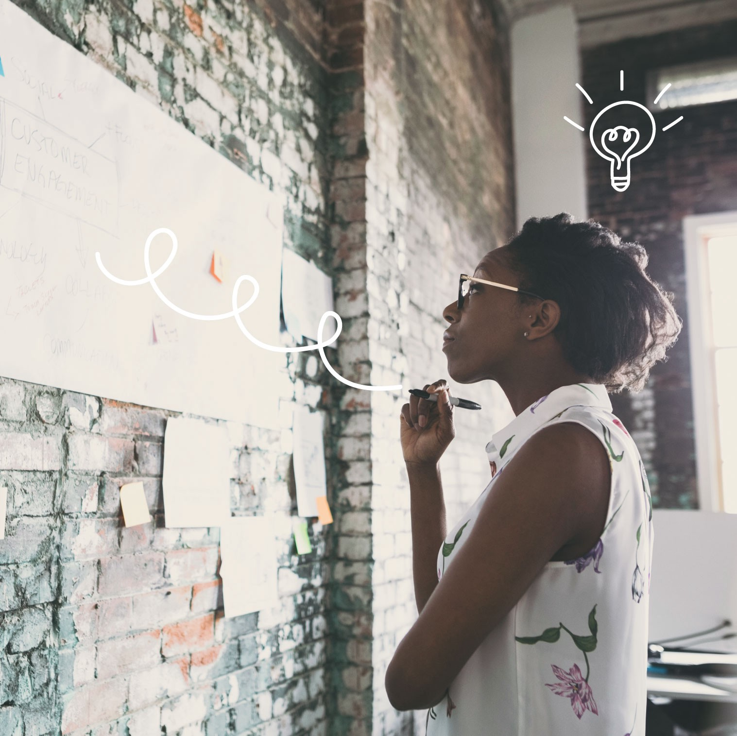 Woman standing in front of wall, writing on a white board