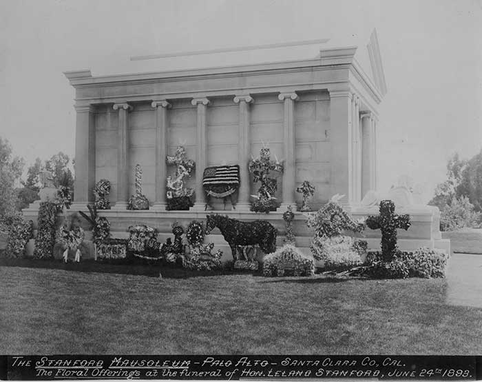 A black and white photo of the mausoleum adorned with fancy topiaries.