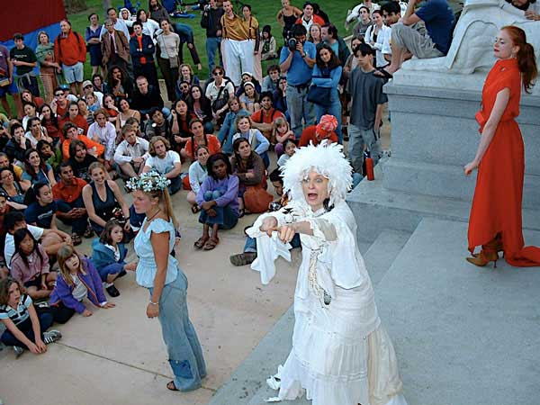 A crowd gathers outside the mausoleum. On its steps are women in strange costumes.
