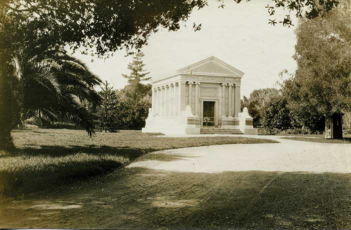 A monotone photo of the mausoleum in a gentle forest.